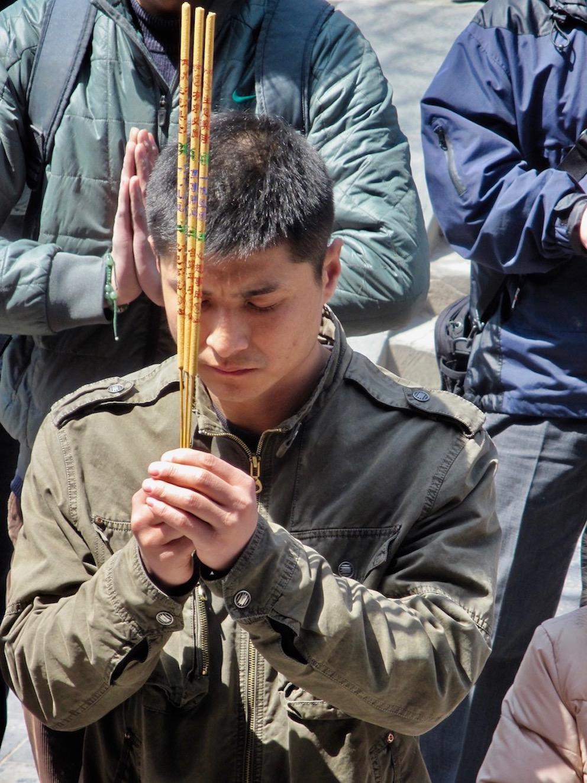Chinese man praying Llama Temple Beijing