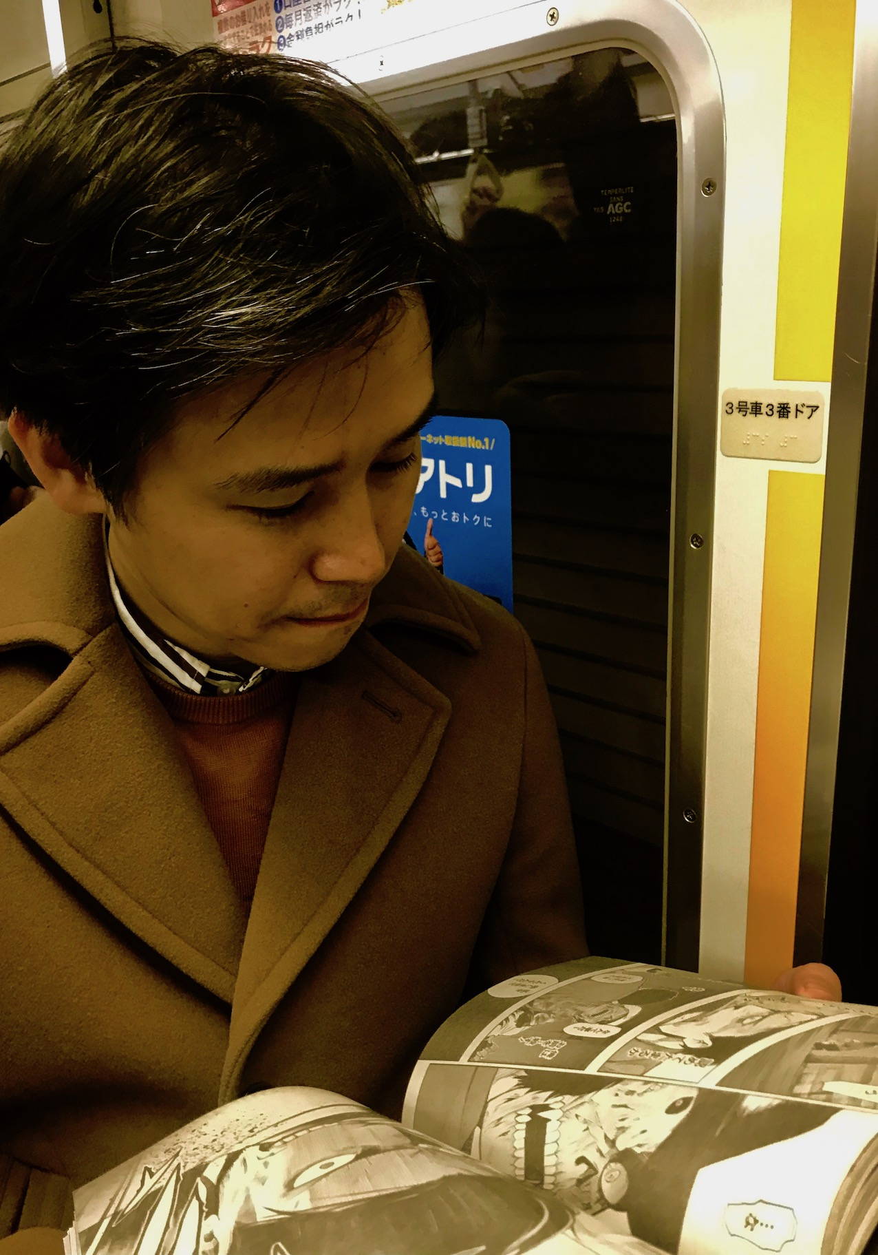 Man reading manga Tokyo Subway Japan.
