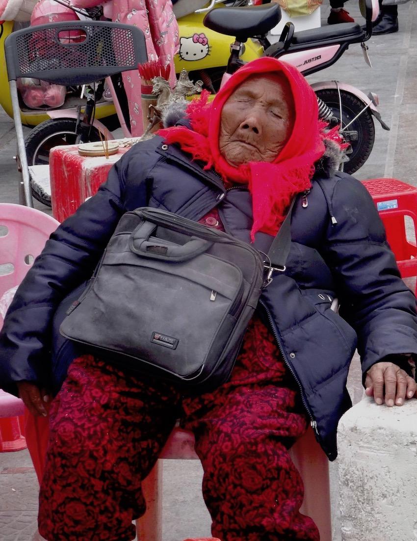 Old woman sleeping Guandi Temple Fujian Province China.