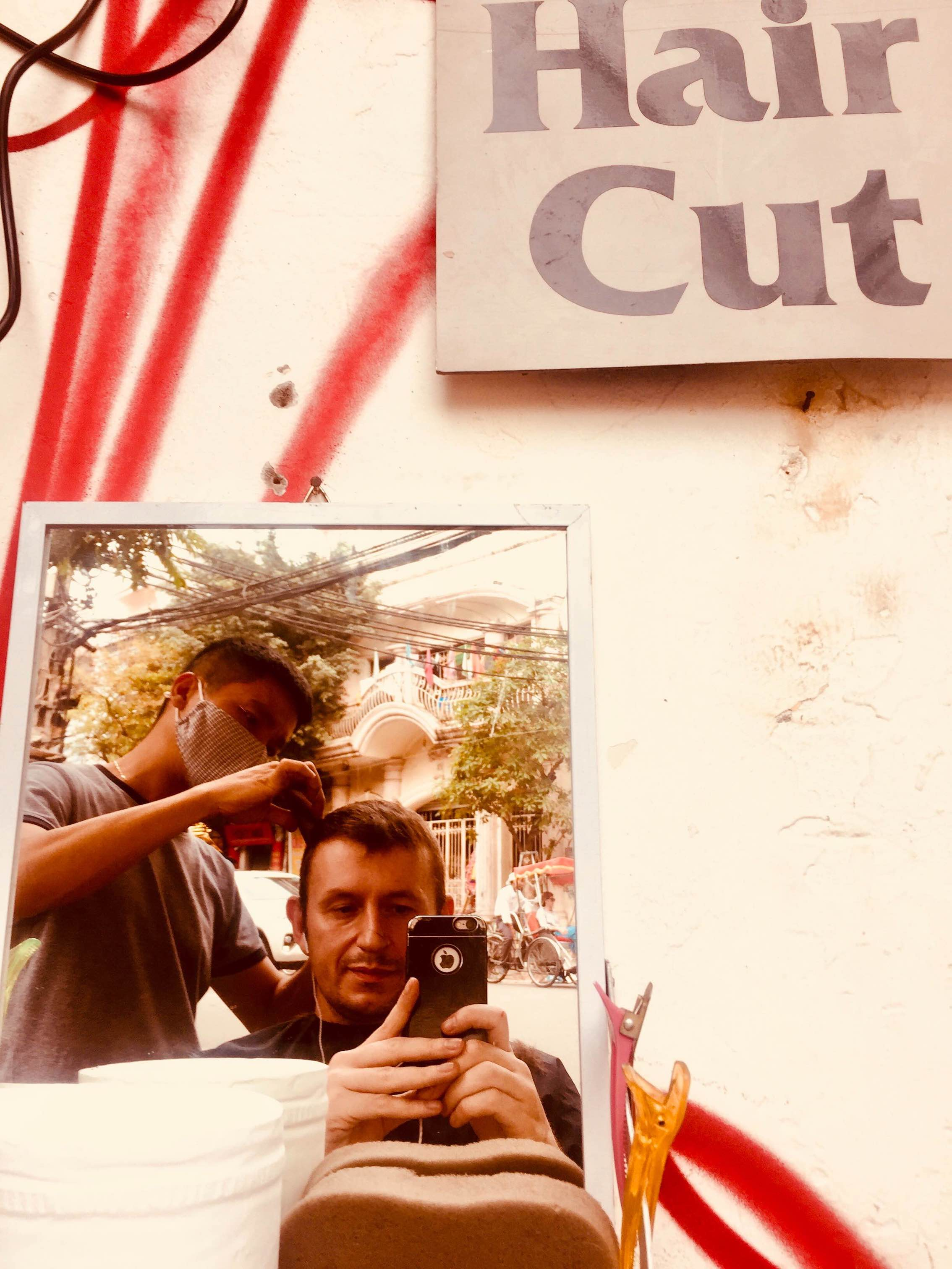Getting a haircut in Hanoi's Old Quarter.