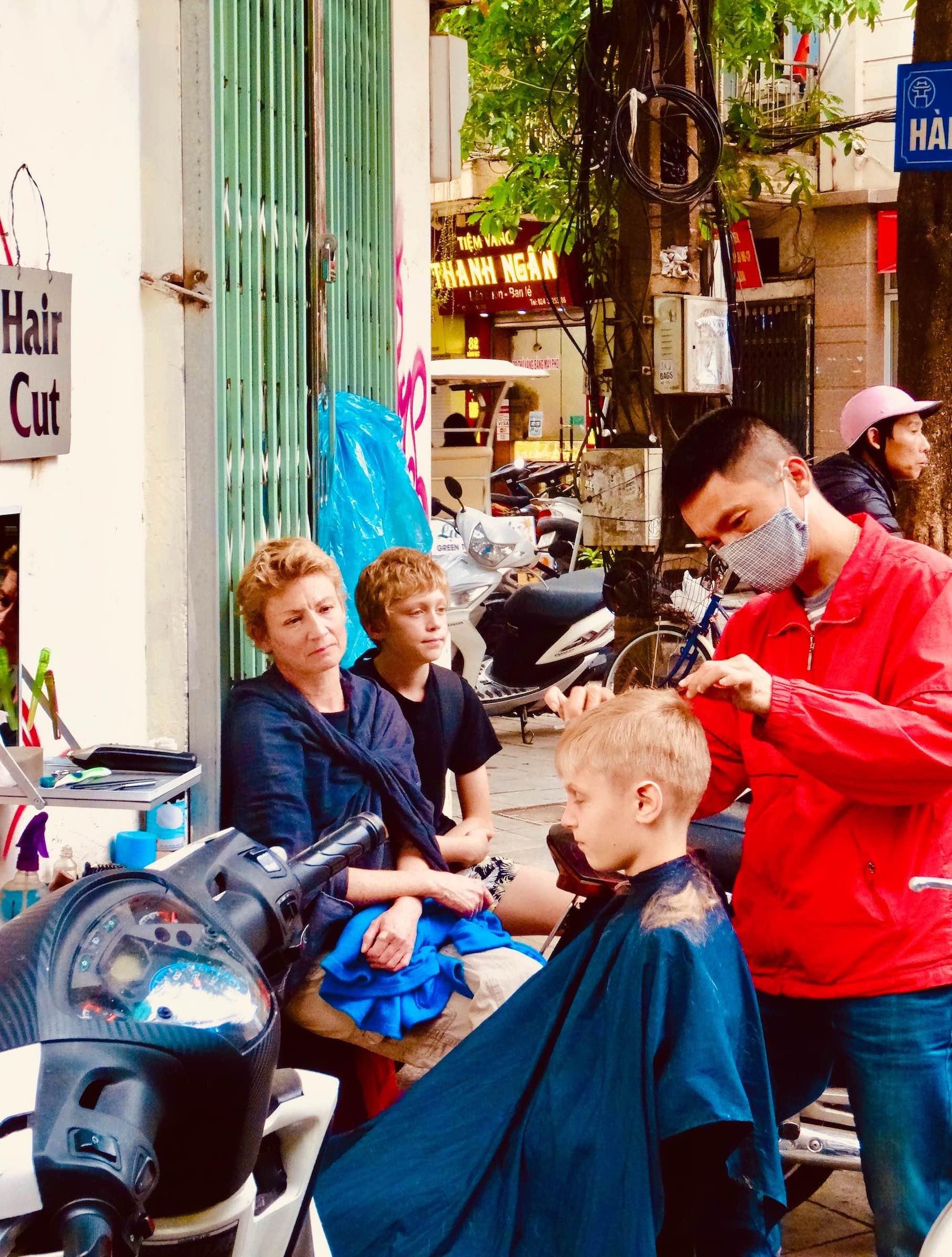 Street hairdresser Hanoi Old Quarter.