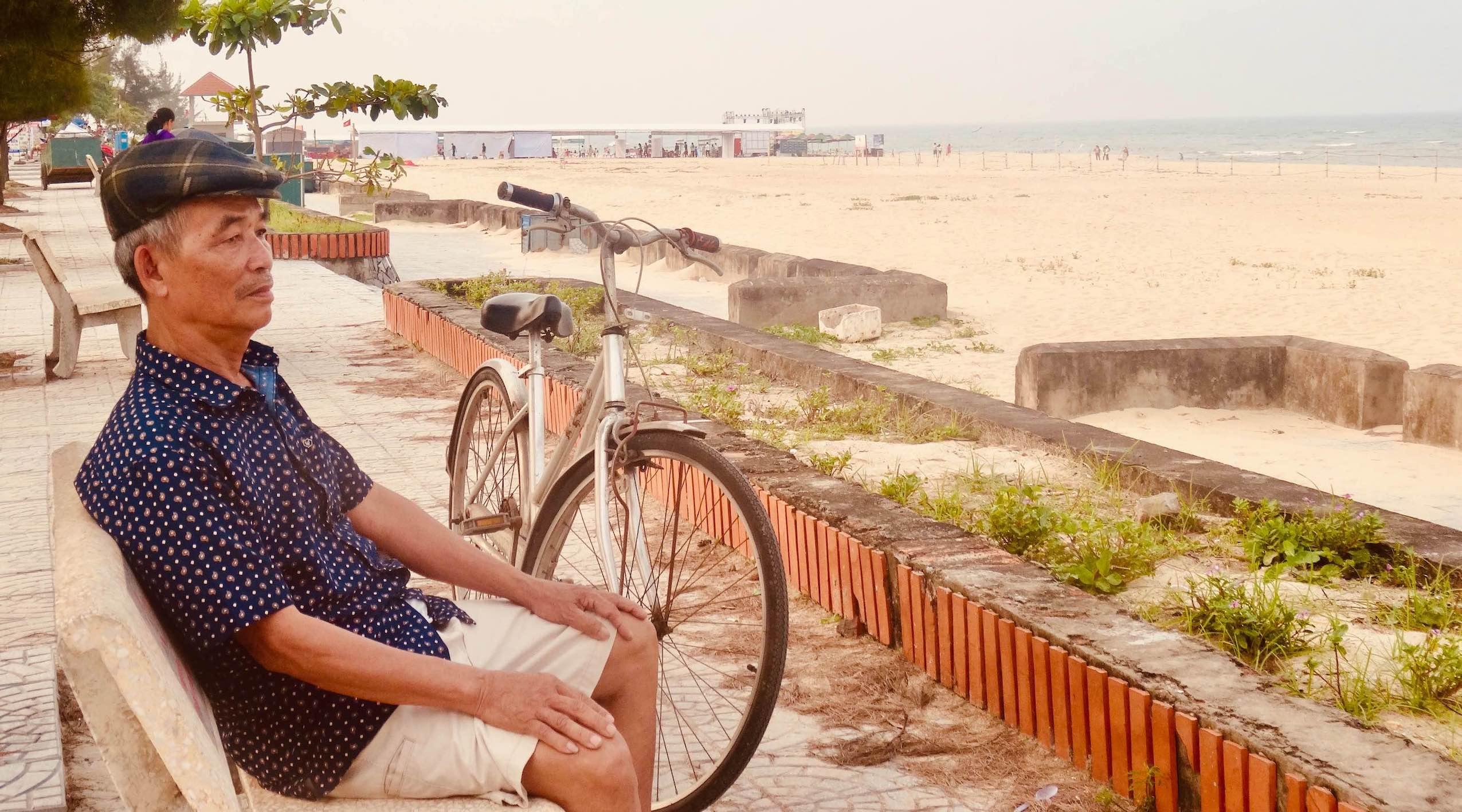 Old man sittin doin nothin Dong Hoi Vietnam