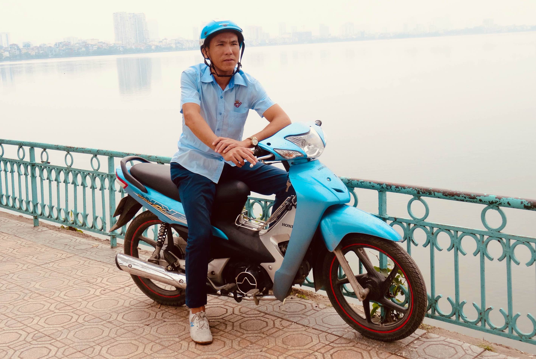 Man on motorbike Ho Tay Lake Hanoi.